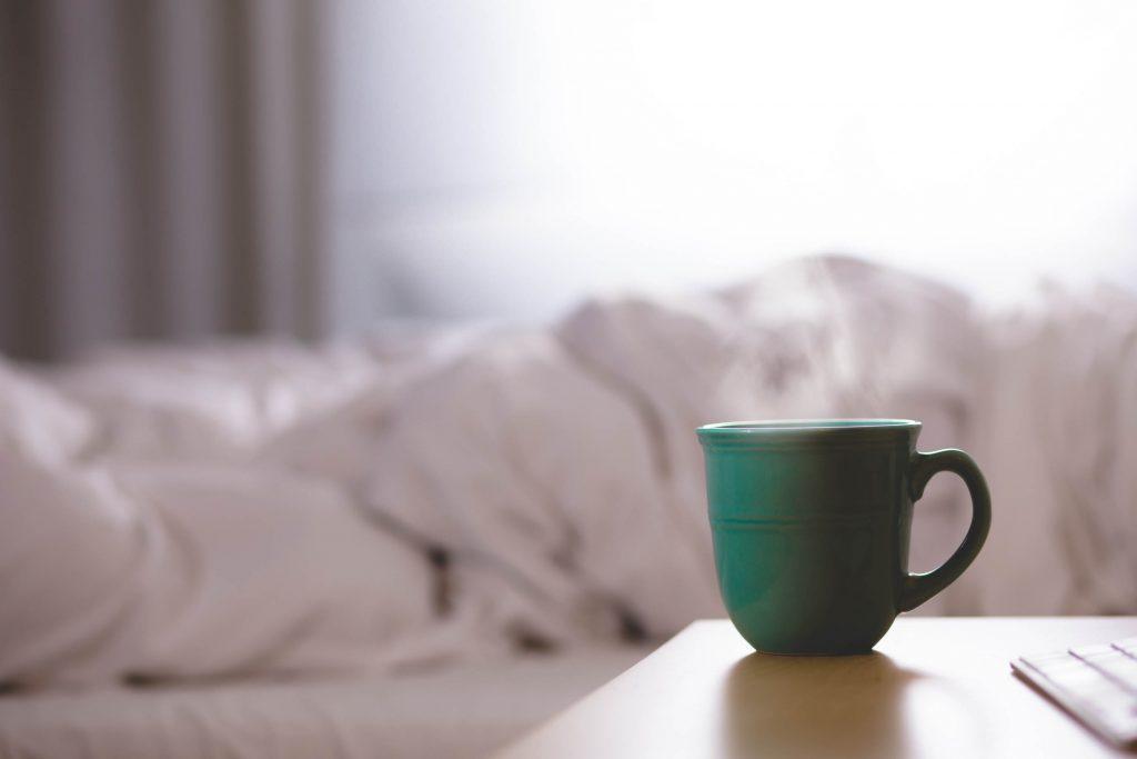 Tasse posées sur table de nuit lit au fond avec malade en hiver