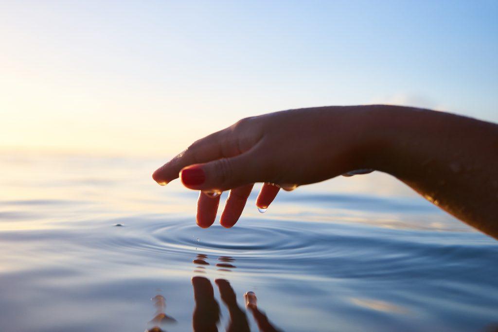 Main qui touche l'eau de la mer