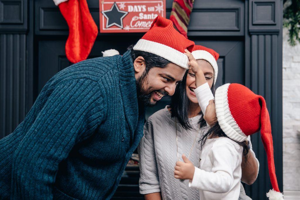 Famille qui rit à essayer des chapeaux de Noel