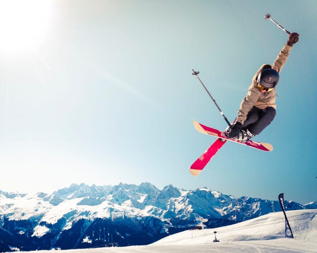 skieur qui fait une figure en l'air sur une pise de ski au sommet d'une montagne